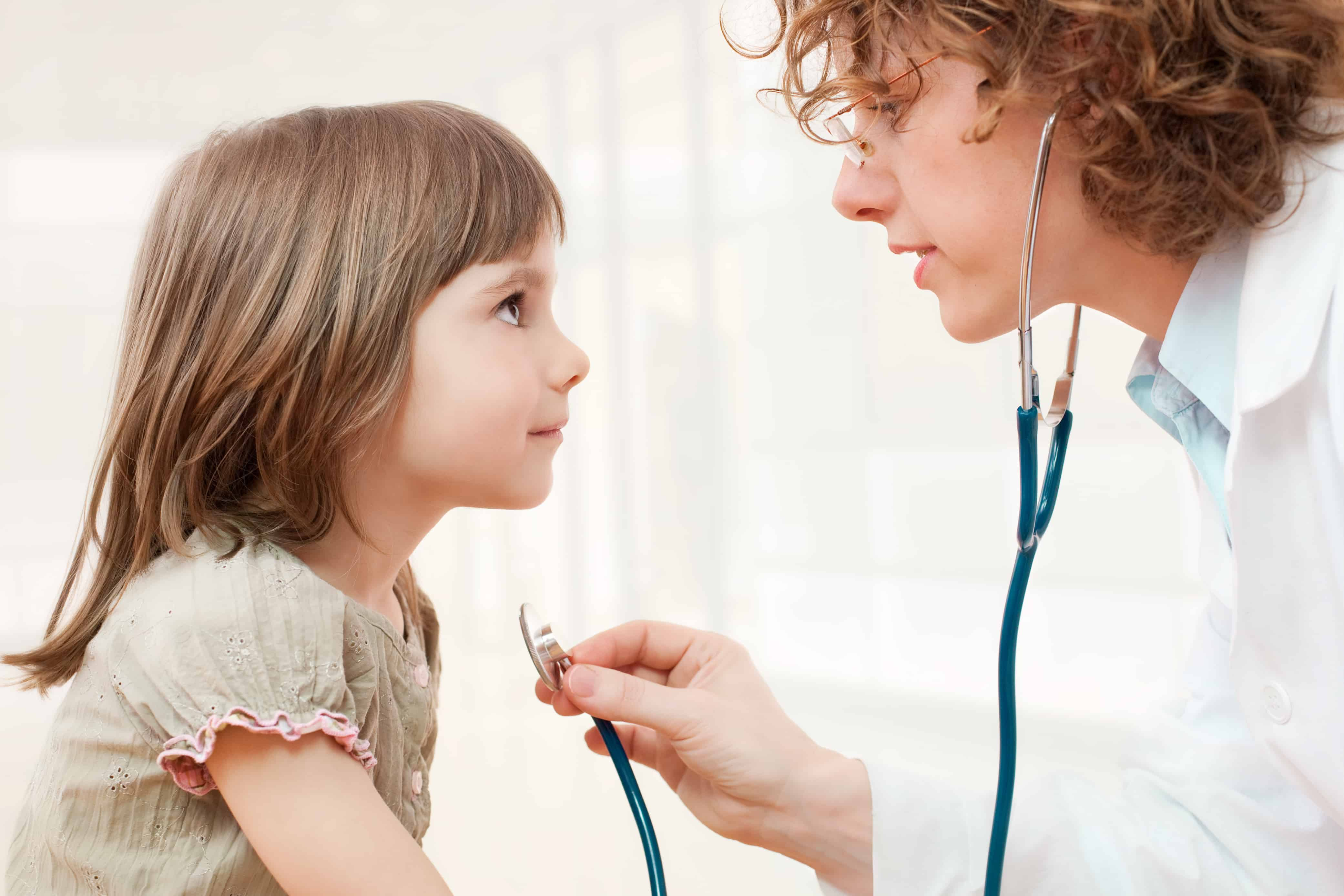 Physician with a stethescope examining a child.
